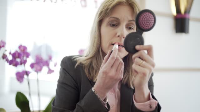 vídeos de stock, filmes e b-roll de a woman in smart city clothes in a cafe with a computer tablet - batom rosa