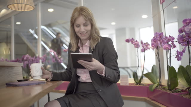 vidéos et rushes de a woman in smart city clothes in a cafe with a computer tablet - seulement des femmes d'âge mûr