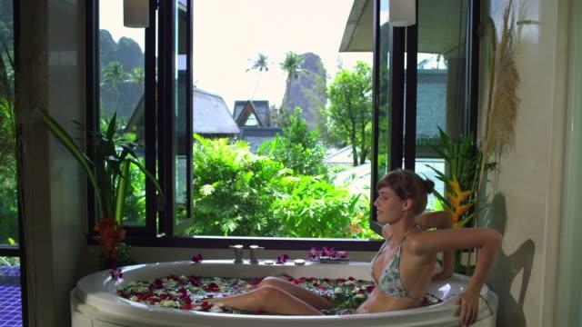ms woman in spa bath with rose-petals, krabi, thailand - verwöhnen stock-videos und b-roll-filmmaterial