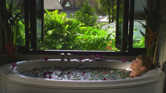 ms woman in spa bath with rose-petals, krabi, thailand - tourist resort stock videos and b-roll footage