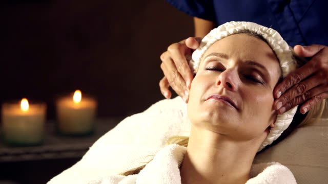 woman in spa getting facial massage - massage table stock videos & royalty-free footage