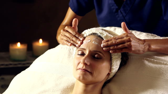 Woman in spa getting facial massage with lotion