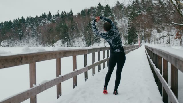a woman in sports clothes is stretching - peter snow stock videos & royalty-free footage