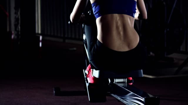woman in sports clothing exercising in the gym - canottaggio video stock e b–roll