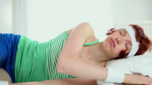 ms woman in sportswear falls onto bed / london, uk - laziness stock videos and b-roll footage