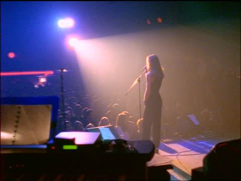 vídeos y material grabado en eventos de stock de rear view woman in spotlight on stage singing to audience - rock moderno