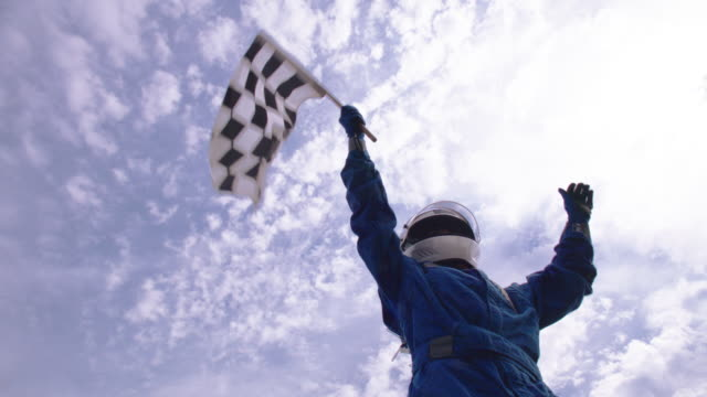 slo mo. woman in stock car helmet waves checkered flag in triumph as blue racing team lifts her up and cheers. - competitive sport stock videos & royalty-free footage