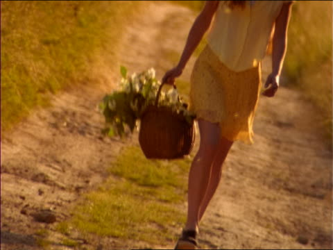 stockvideo's en b-roll-footage met canted woman in straw hat walking in countryside with basket of flowers / smiles + points at camera - strohoed
