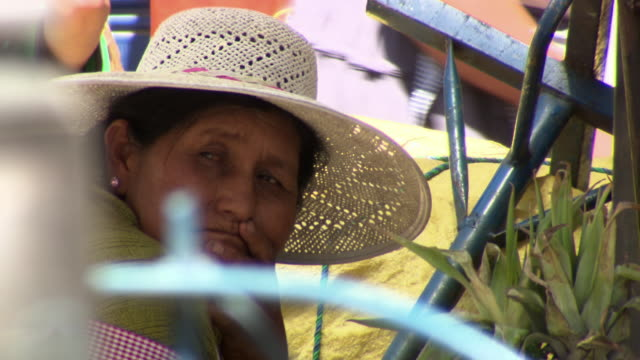 cu of woman in straw hat watching the world, la cancha market, cochabamba, bolivia - straw hat stock videos and b-roll footage