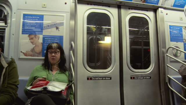 MS SHAKY Woman in subway train listening to mp3 player / New York City, New York, USA