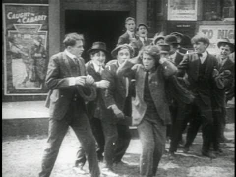 B/W 1914 woman in suit (Minta Durfee) running away from crowd of men standing outside of building