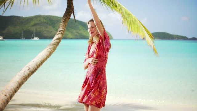 woman in sundress dancing on beach enjoying the sun on virgin islands - st. john virgin islands stock videos & royalty-free footage