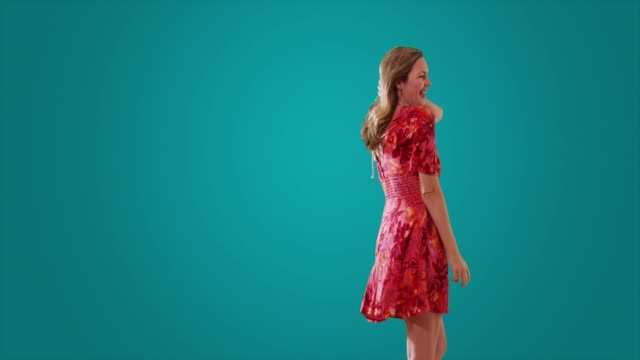 stockvideo's en b-roll-footage met woman in sundress dancing on blue background with copyspace - vaste stof