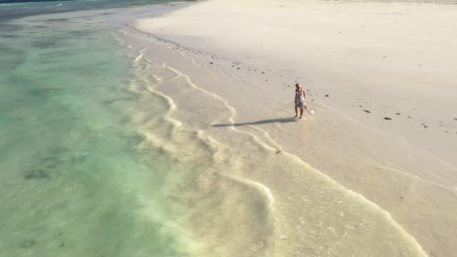 aerial woman in sundress walking along beautiful beach - sundress stock videos & royalty-free footage