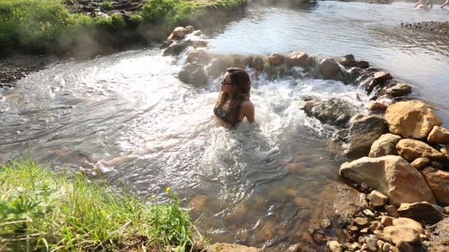 woman in sunglasses relaxes in hot spring, looking into the distance - spa treatment stock videos & royalty-free footage