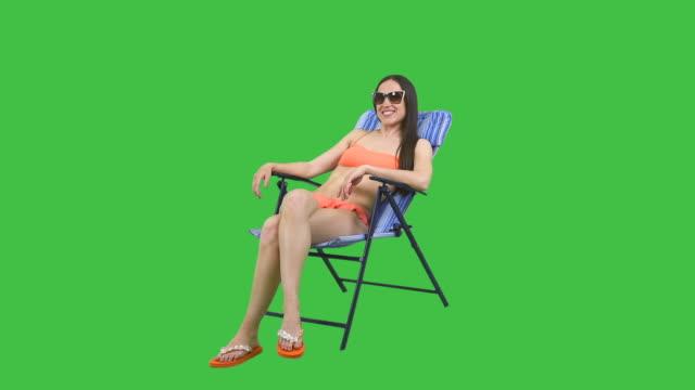 Woman in sunglasses sunbathing in lounge