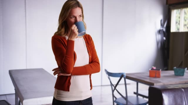 woman in sweater drinking from coffee mug inside garage, looking off camera - coffee drink stock videos & royalty-free footage