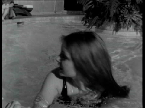 Woman in swimming pool at Playboy mansion / Man awkwardly lifting woman out of pool Playboy Mansion on February 02 1966 in Chicago Illinois