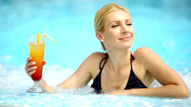 Woman in swimming pool having a cocktail.