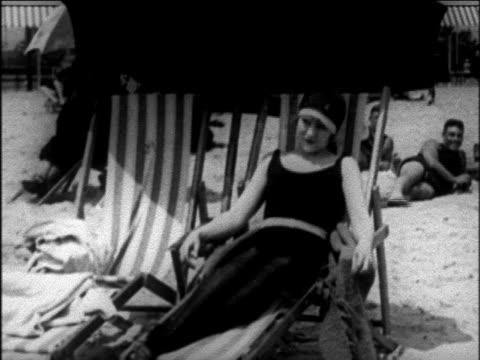 vídeos de stock, filmes e b-roll de b/w 1925 woman in swimsuit + dark stockings sitting in deck chair on beach / newsreel - cadeira de praia