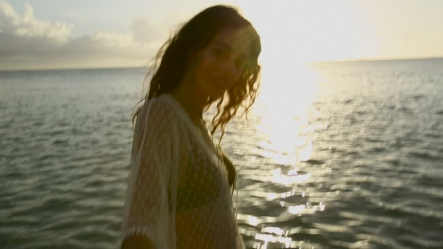 vidéos et rushes de woman in swimsuit holds hands at sunset in tahiti, point of view - maillot de bain