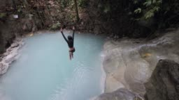 A woman in swimsuit jumping off the edge of waterfall into a turquoise water.