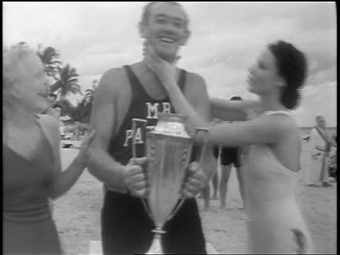 b/w 1937 woman in swimsuit kissing cheek of winner in lifeguard beauty contest / florida / newsreel - trophy award stock videos & royalty-free footage