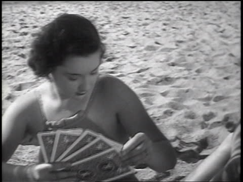 B/W 1937 woman in swimsuit playing game with large cards on beach / newsreel