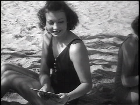 vidéos et rushes de b/w 1937 woman in swimsuit reaching for card in card game on beach / newsreel - maillot une pièce