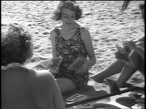 B/W 1937 woman in swimsuit setting down card in card game on beach / newsreel