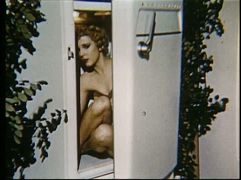 woman in swimsuit sitting in refrigerator opens door - whatif点の映像素材/bロール