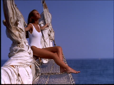 woman in swimsuit sitting on sail of boat - swimming costume stock videos and b-roll footage
