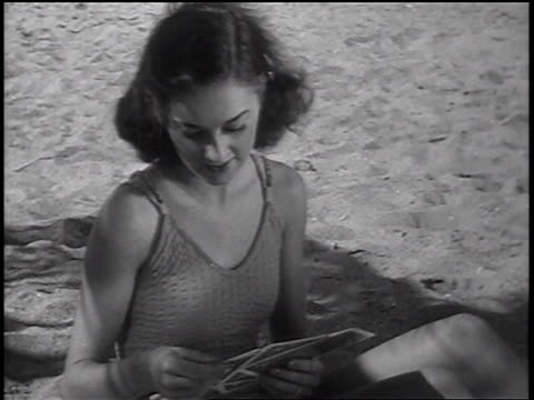 vidéos et rushes de b/w 1937 woman in swimsuit sitting + playing cards on beach / newsreel - maillot une pièce