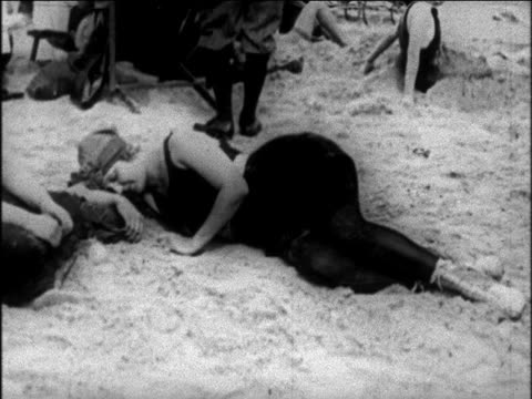 b/w 1925 woman in swimsuit sleeping on beach / newsreel - 1925 stock videos & royalty-free footage