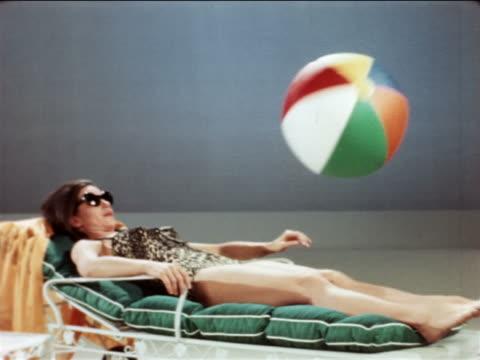 vídeos y material grabado en eventos de stock de 1967 woman in swimsuit sunbathing on lounge chair in studio / beach ball hits her + she smiles - tumbona