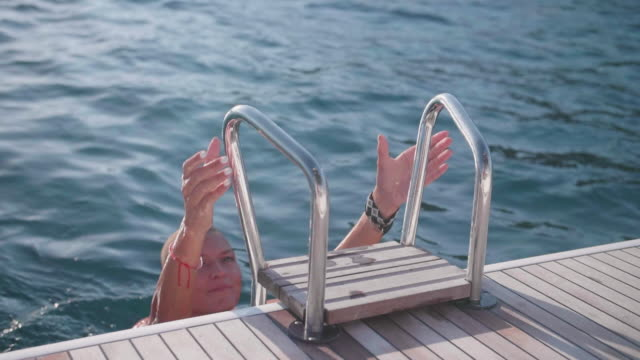 stockvideo's en b-roll-footage met woman in swimsuit swimwear bikini swimming and climbing a ladder on a sailboat boat in greece. - ladder gefabriceerd object