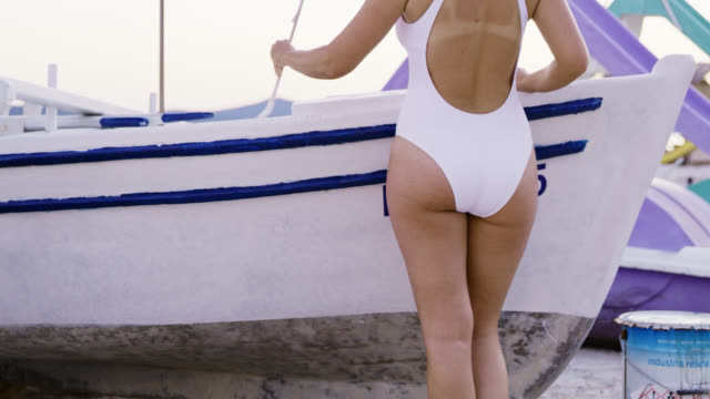 ds woman in swimwear painting a boat - mid adult stock videos & royalty-free footage