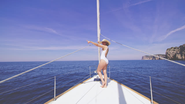 WS Woman in swimwear pointing at something on a sailboat