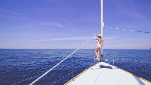 WS Woman in swimwear pointing at something while sailing