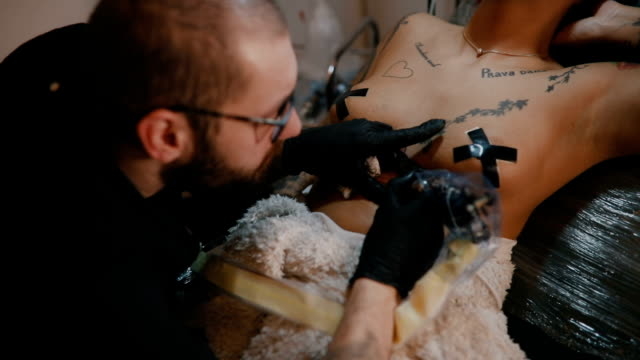 vídeos de stock e filmes b-roll de woman in tattoo studio - nu