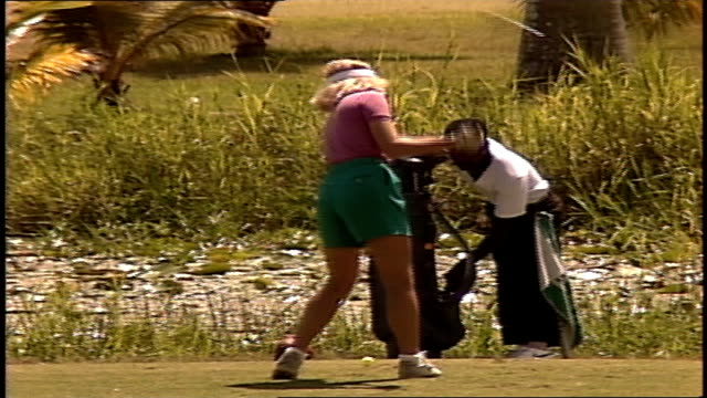 Woman in Teal Shorts Playing Golf at Resort as Seen Through Leaves in Jamaica