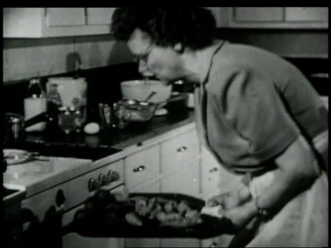 1948 MONTAGE Woman in test kitcheen taking food out of an oven and moving pieces to plate / New York City, New York, United States