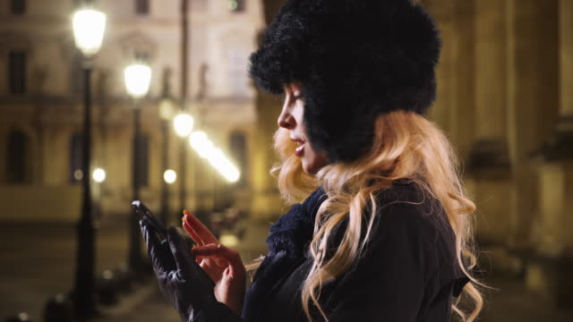 Woman in the city at night types a message to her friend with mobile phone
