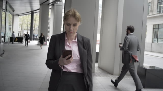 A woman in the city walking and browsing her phone