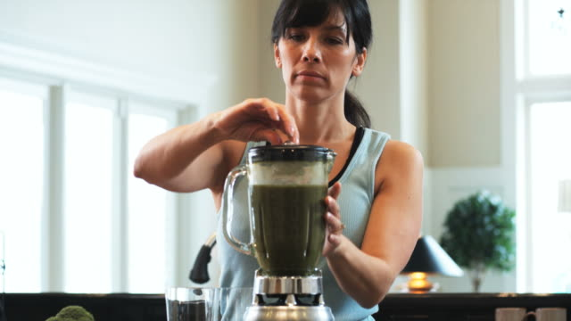 woman in the kitchen making a green smoothie in the blender  - one mid adult woman only stock videos & royalty-free footage