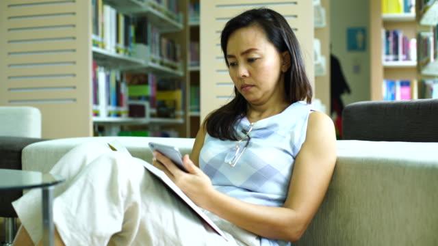 vídeos de stock e filmes b-roll de woman in the library - óculos de leitura