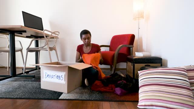 vídeos y material grabado en eventos de stock de mujer en la oficina doblando ropa para la donación. - sólo mujeres jóvenes