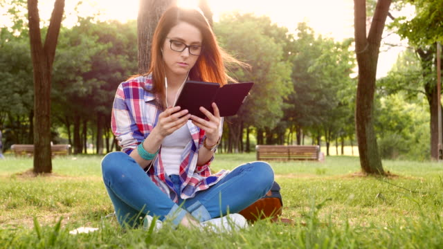 woman in the park reading an e-book - e book stock videos & royalty-free footage