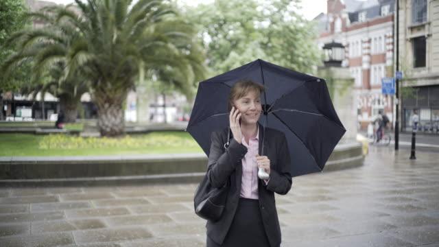 9-5 woman in the rain - formelle geschäftskleidung stock-videos und b-roll-filmmaterial