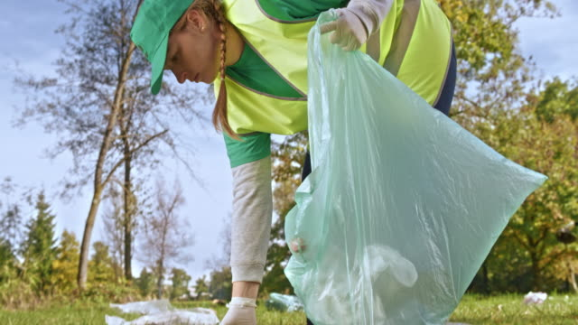 woman in the regional clean up group picking up rubbish scattered across a meadow - volunteer stock videos & royalty-free footage